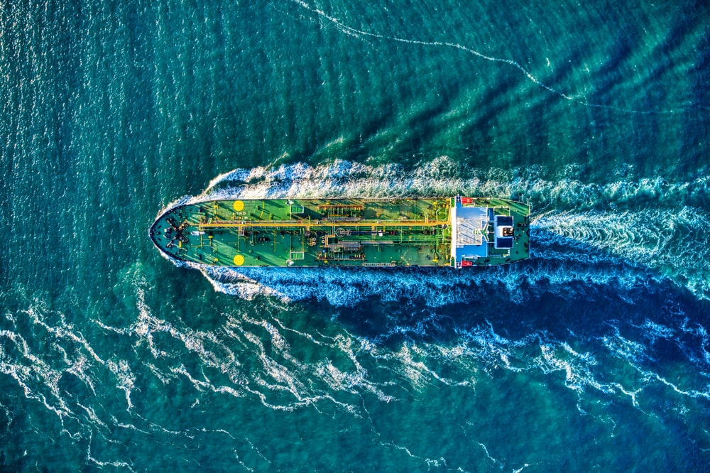 aerial view of white and yellow boat on body of water during daytime