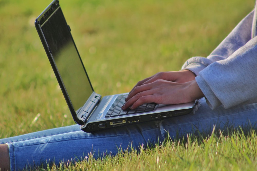 person in blue denim jeans using black laptop computer on green grass field during daytime
