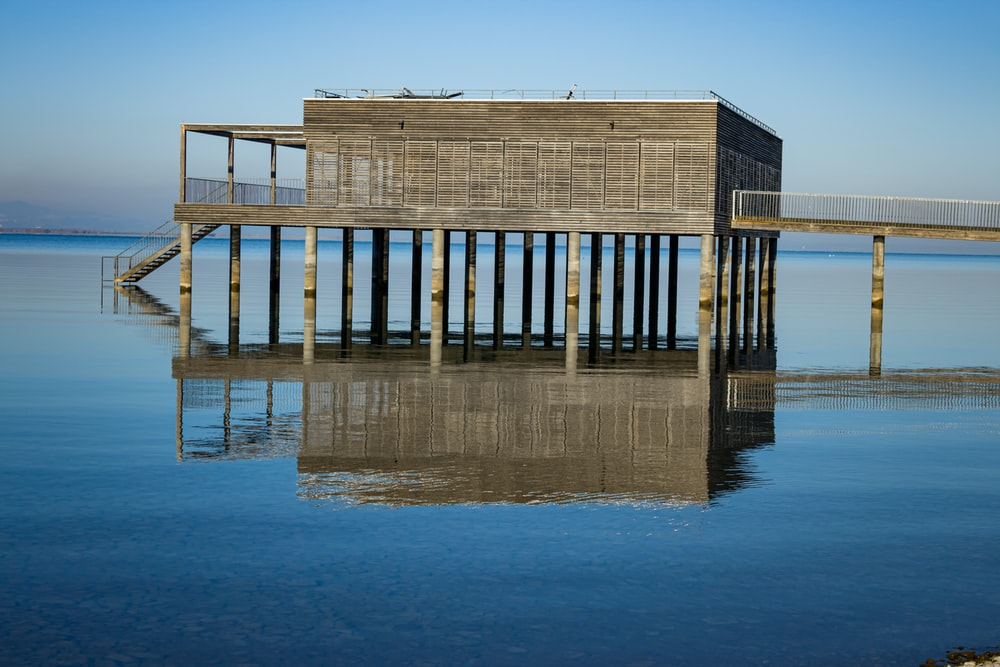 brown wooden dock on blue sea during daytime