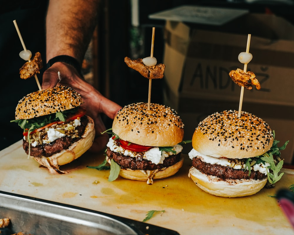 person holding burger with patty and cheese