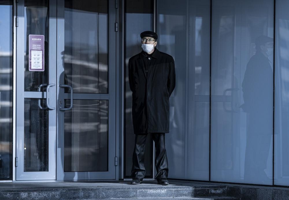 man in black coat standing beside glass door