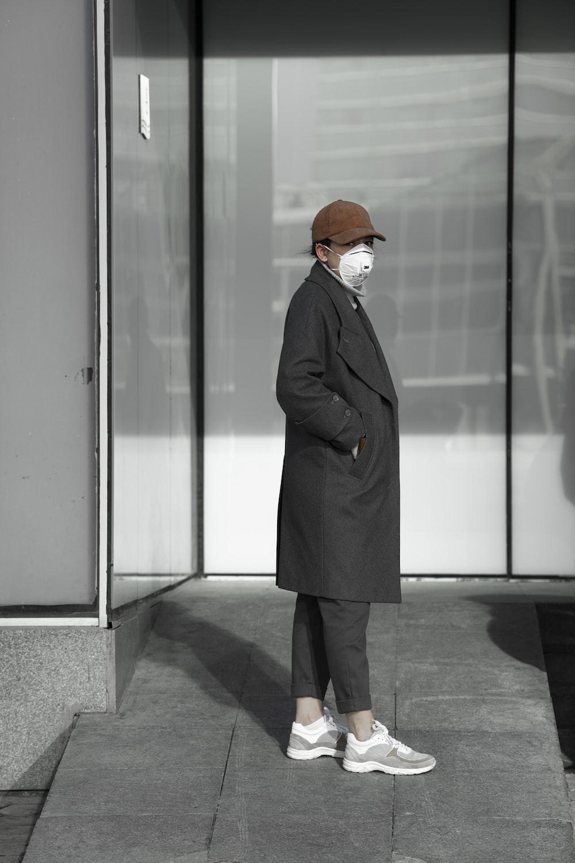 woman in black coat standing in front of glass door