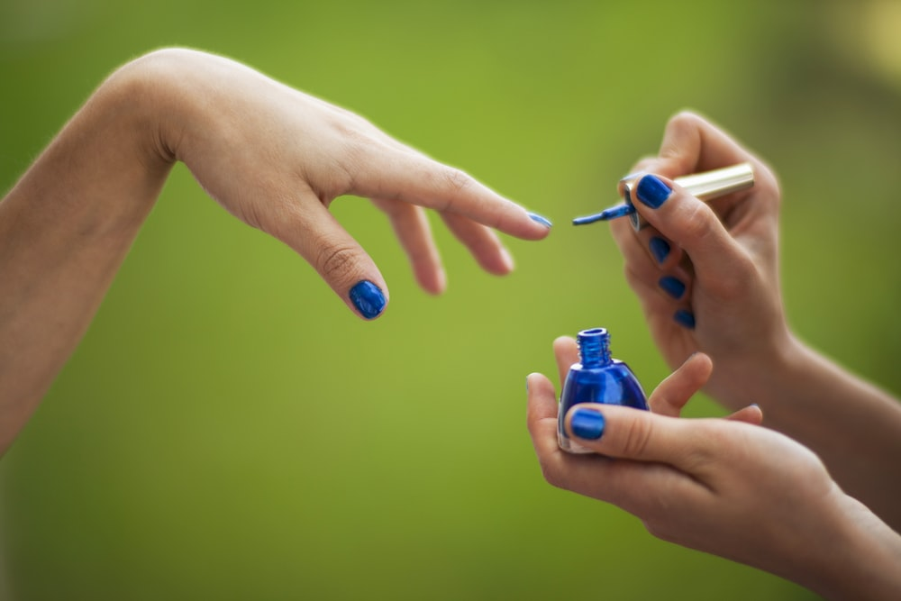person holding blue and white plastic bottle