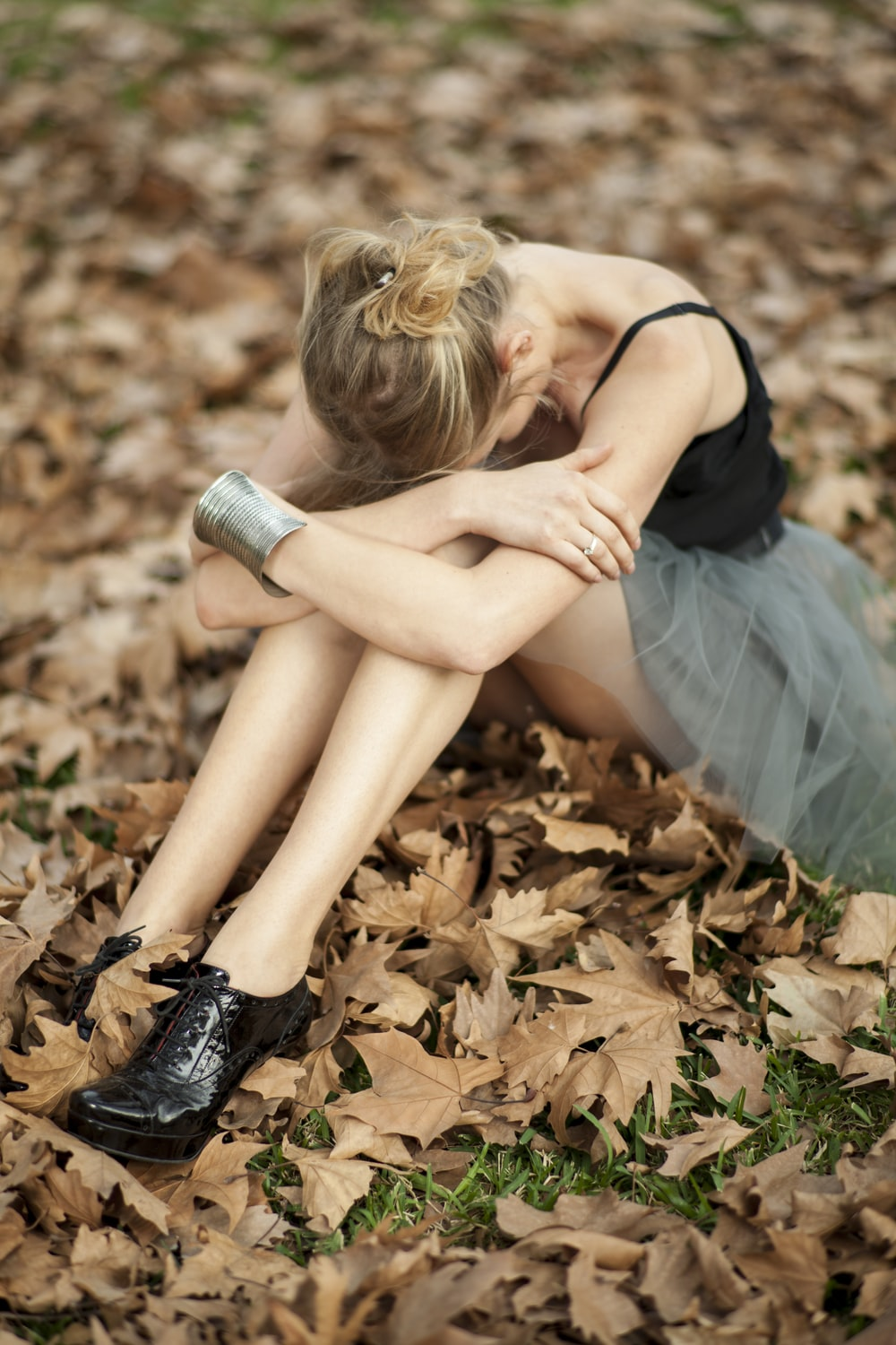 woman in black tank top and blue skirt sitting on dried leaves