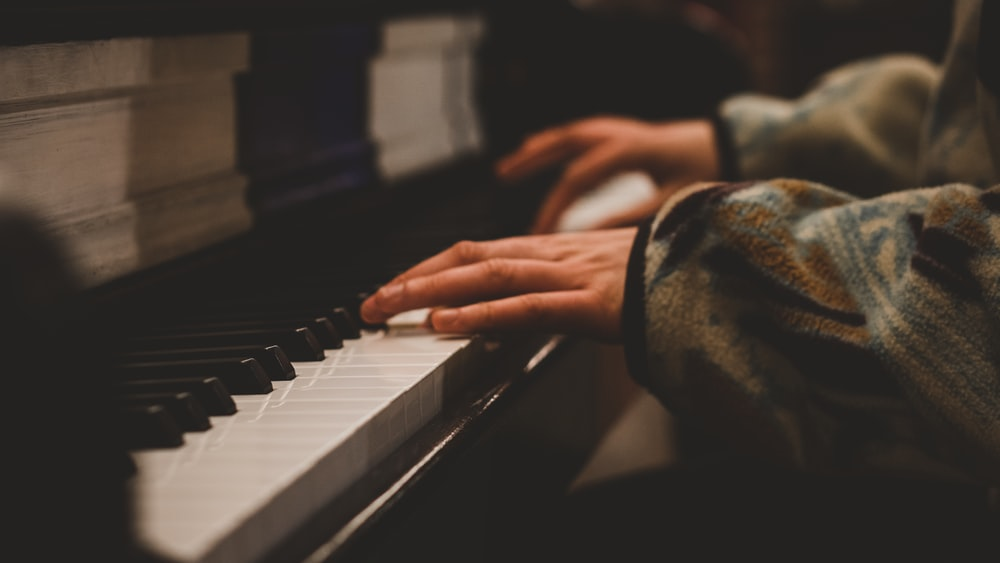 person playing piano in grayscale photography