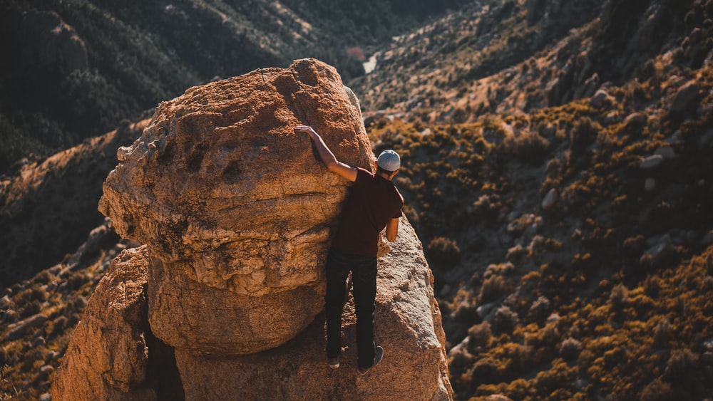 man in black jacket and black pants standing on brown rock formation during daytime