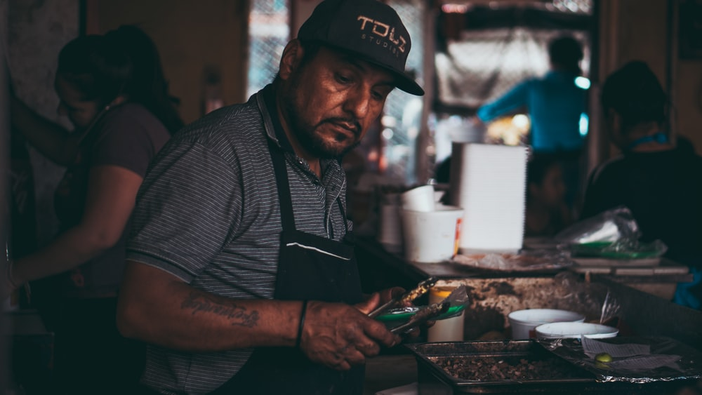 man in black and white stripe shirt wearing black cap