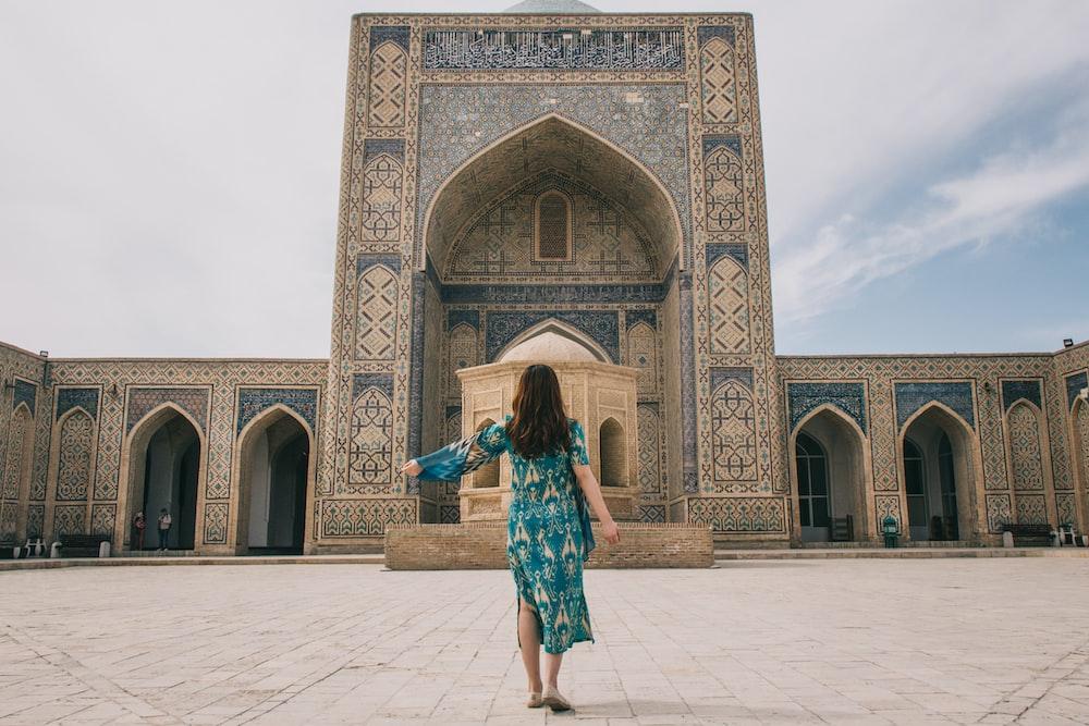 woman in teal dress standing on brown brick floor
