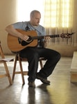 man in gray polo shirt playing brown acoustic guitar