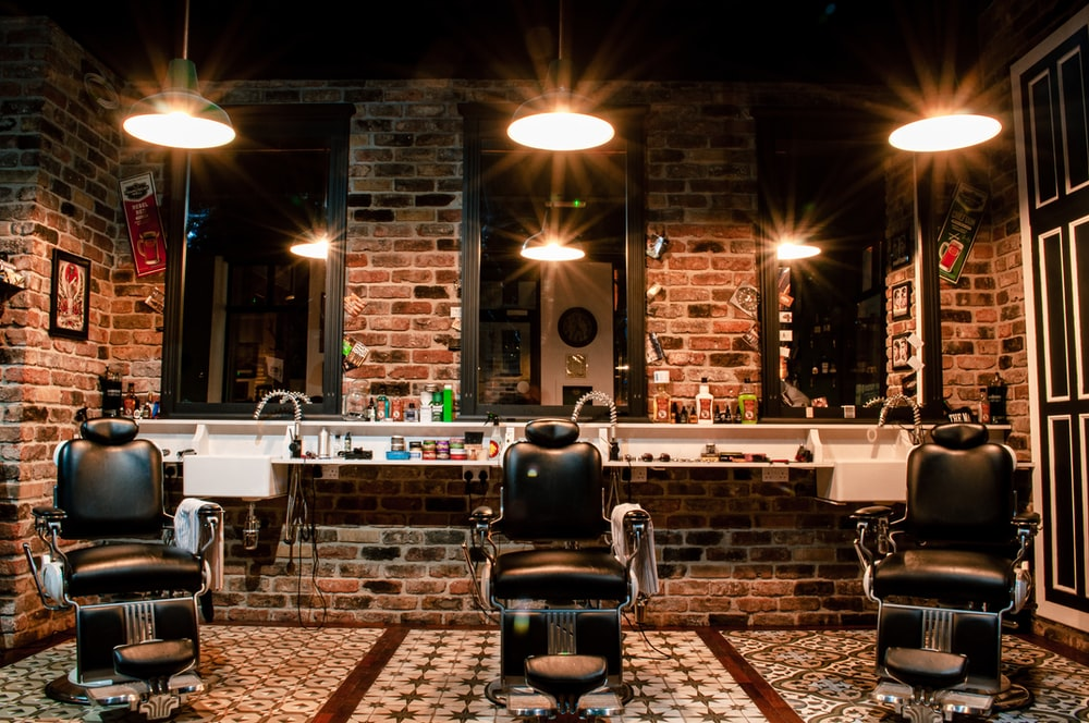 black leather barber chair near brown brick wall