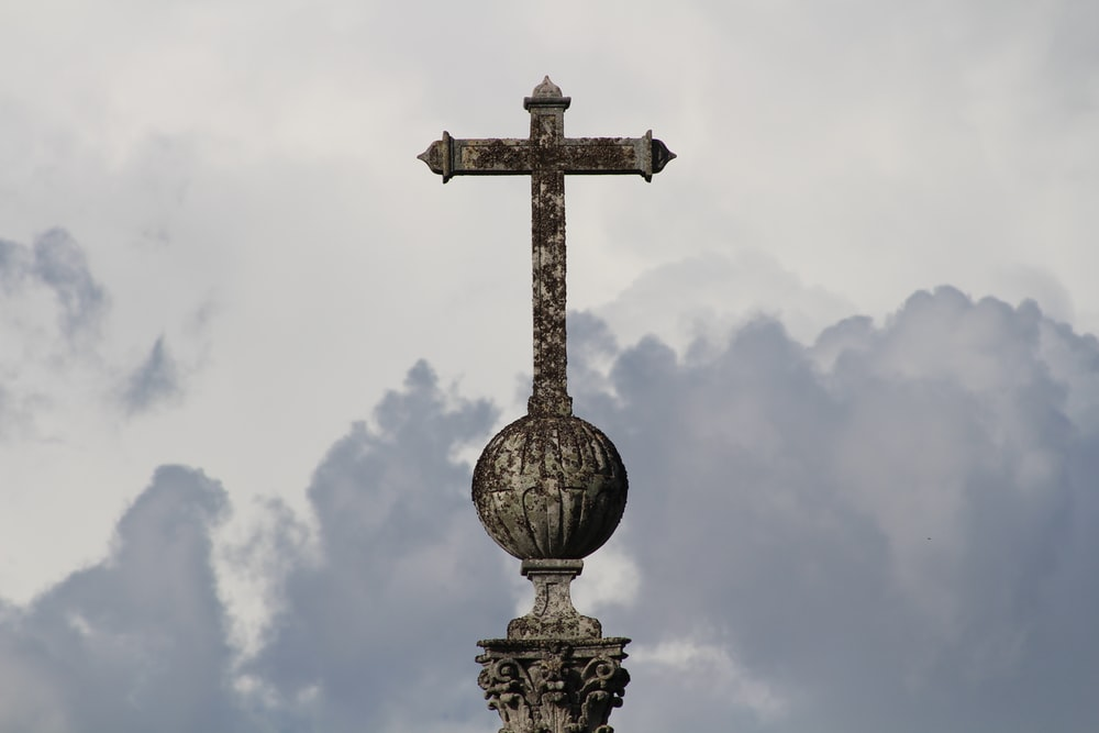 gold cross statue under white clouds during daytime