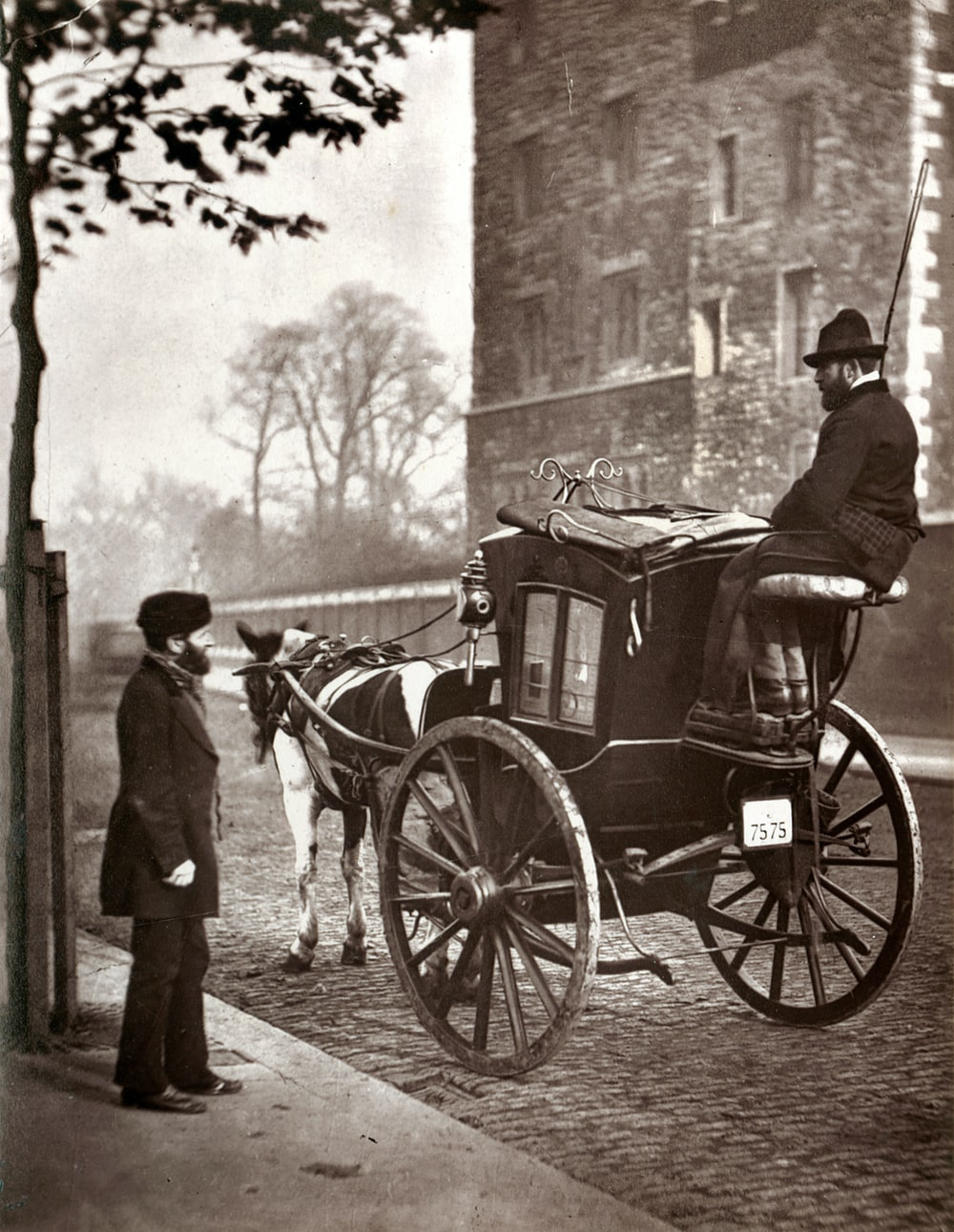 man in black coat standing beside horse carriage in grayscale photography