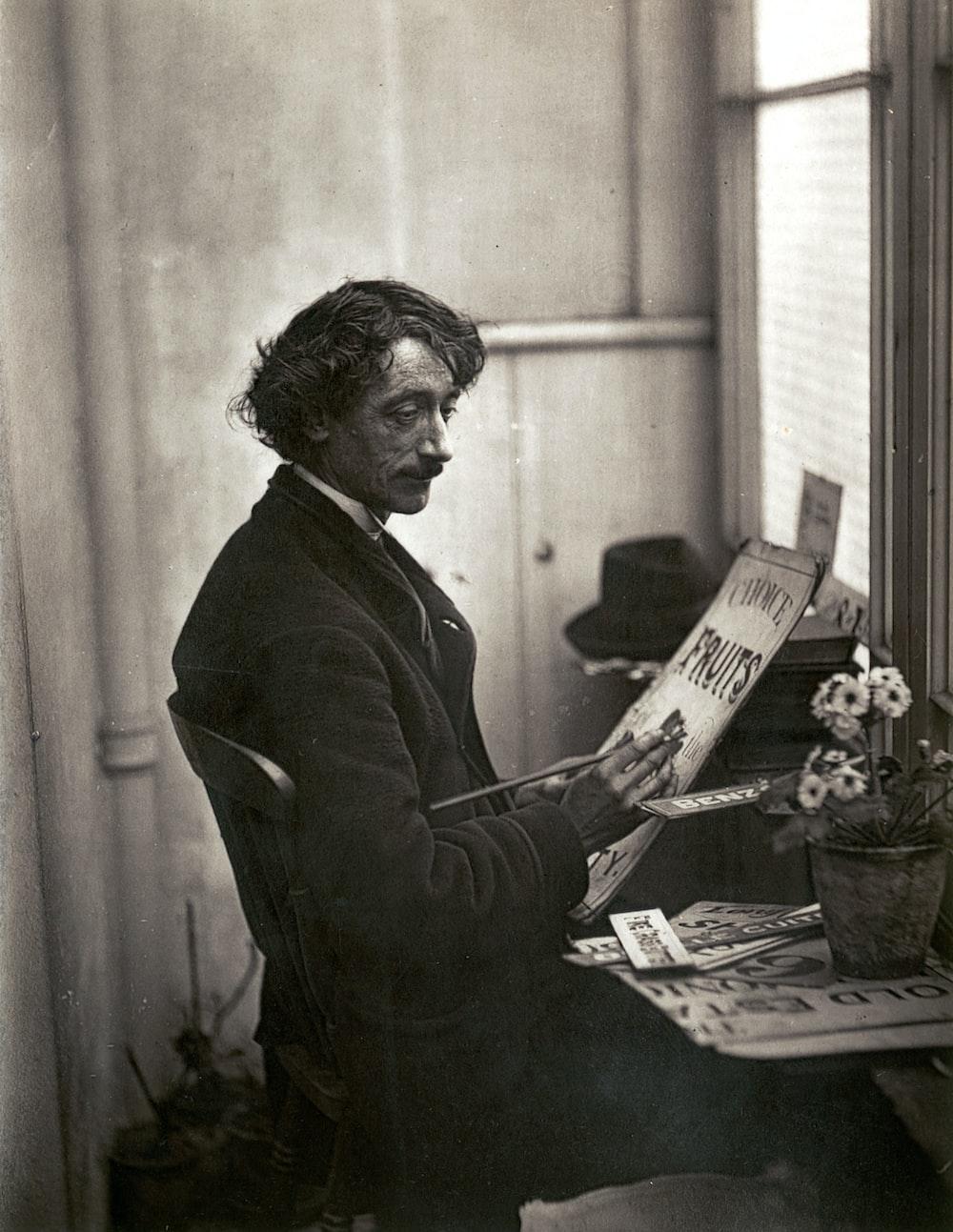 man in black suit jacket reading newspaper