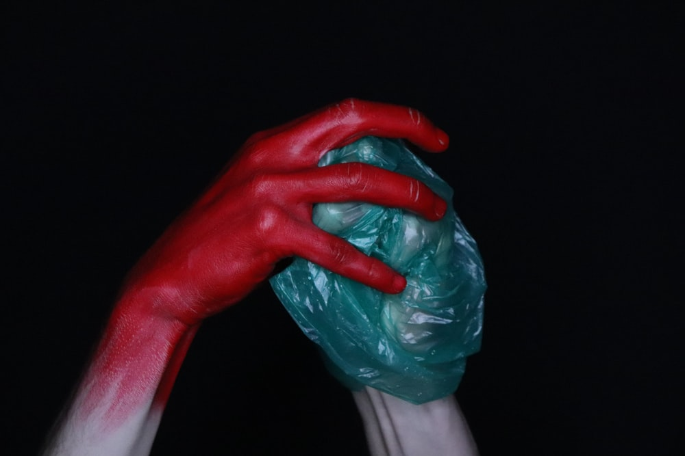 person holding red plastic bag