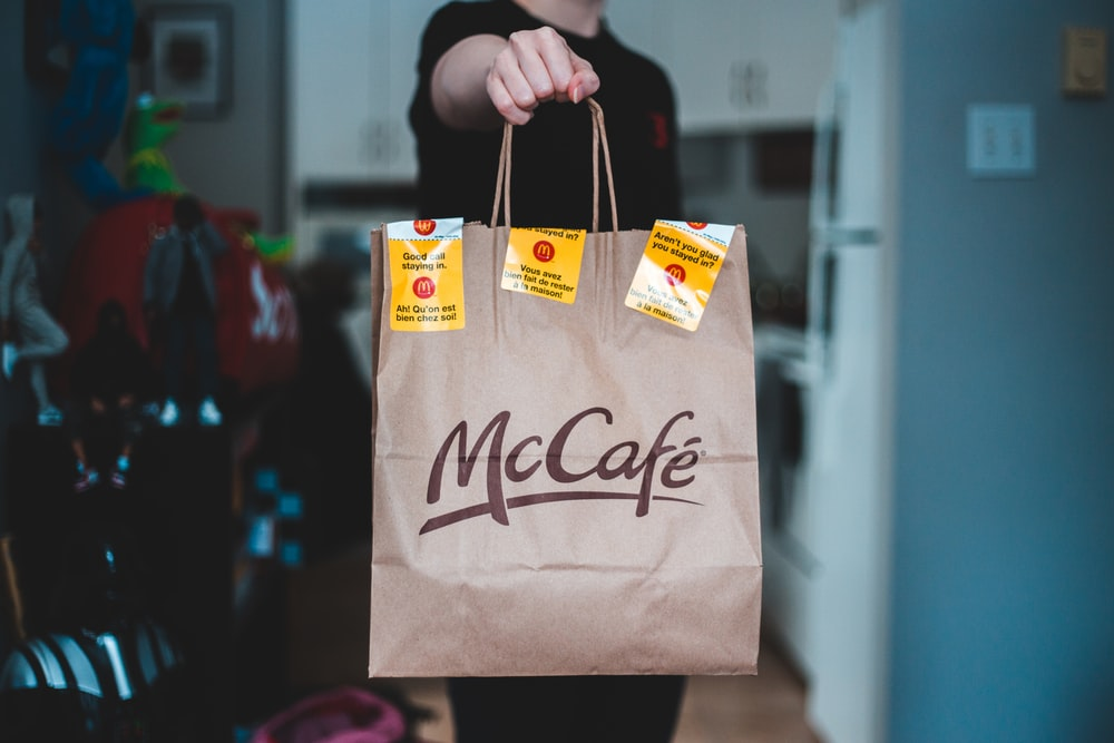 person holding white and brown paper bag