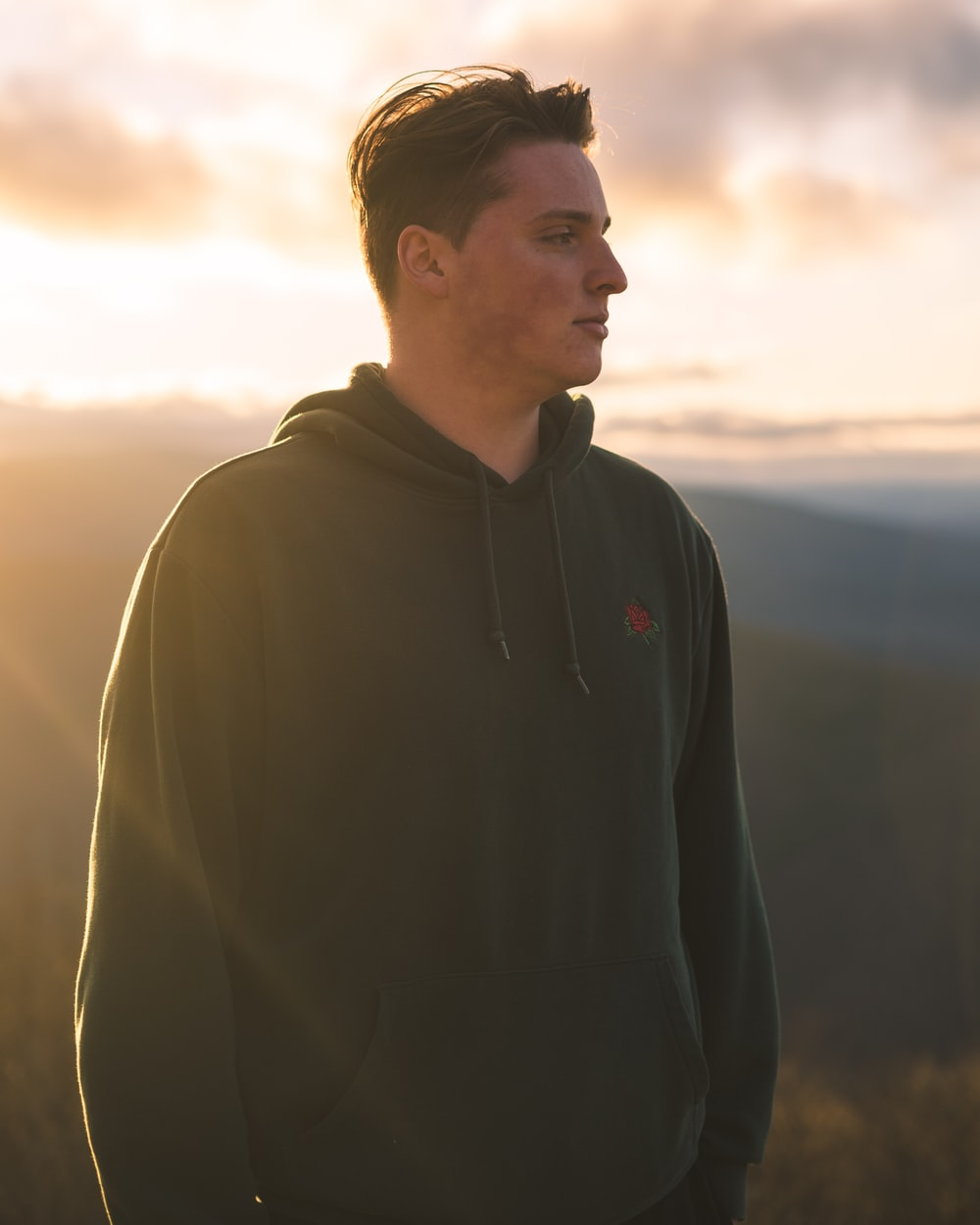man in black hoodie standing on hill during daytime