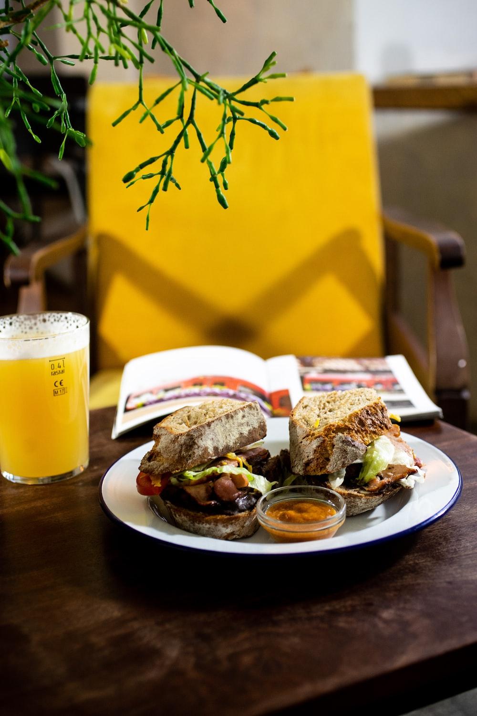 burger on white ceramic plate beside drinking glass