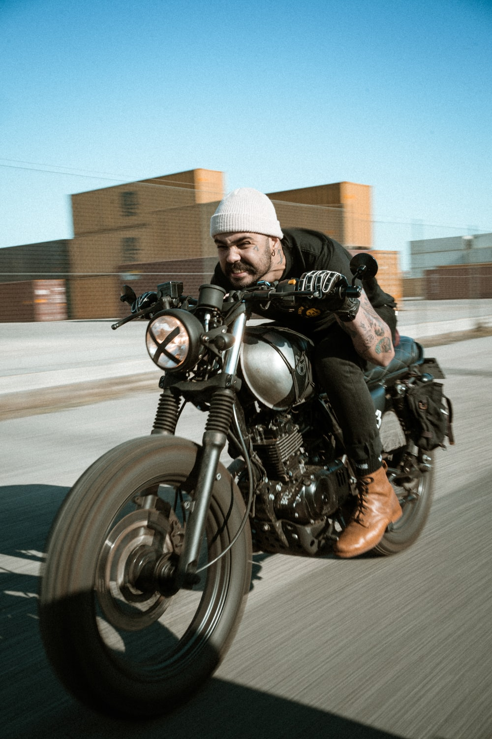 man in black leather jacket and knit cap riding black motorcycle