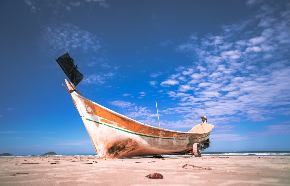 brown and white boat on brown sand under blue sky during daytime