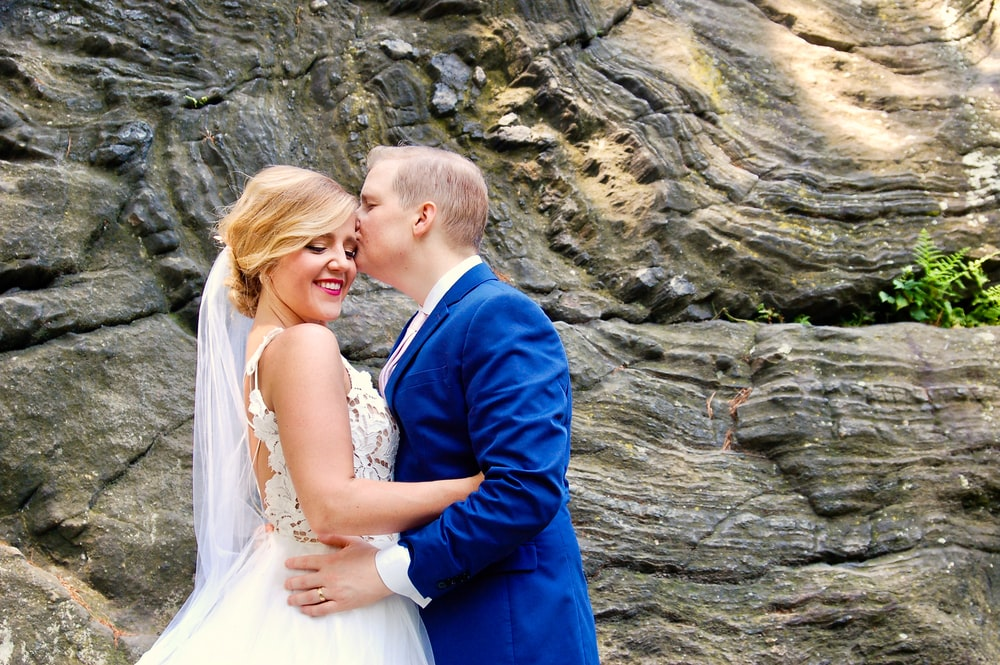 man in blue suit jacket kissing woman in white wedding dress
