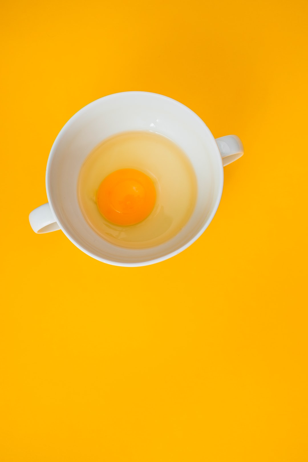 Fresh chicken  egg in ramekin on yellow background. Large copy space. Top view