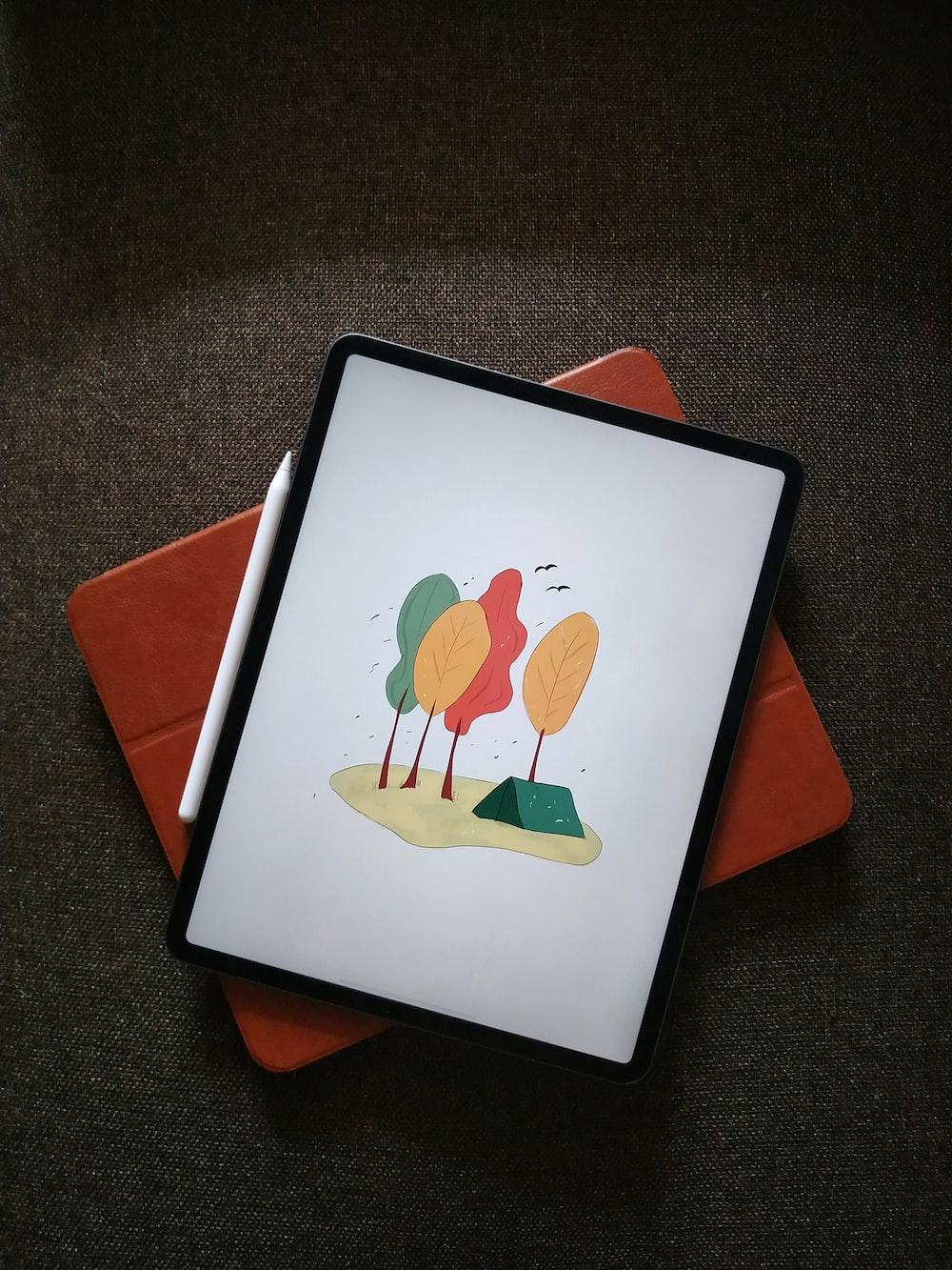 white ipad on orange textile