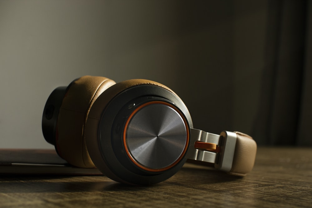 white and black headphones on brown wooden table