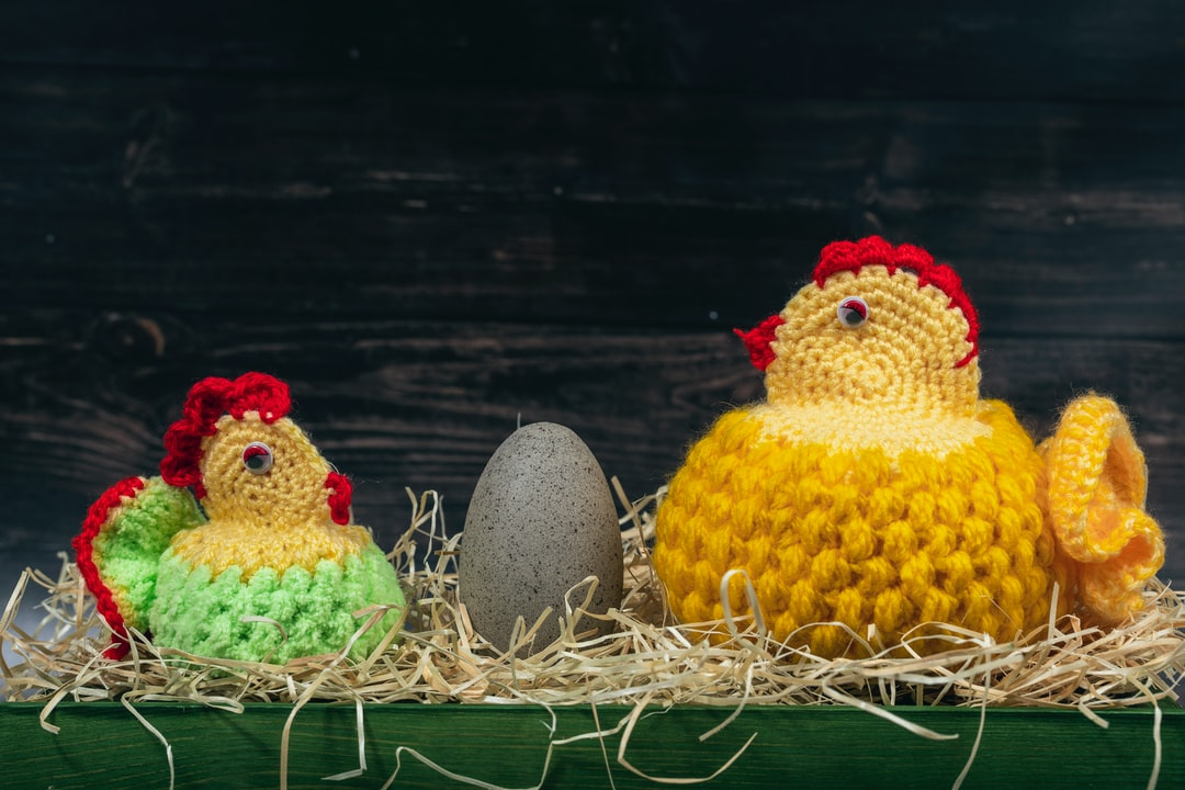 Two handmade knitted woolen Easter chickens with rock egg in front of a wooden wall. Easter time.