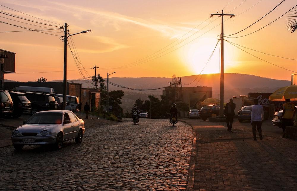 people walking on sidewalk during sunset