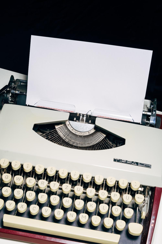 white and black typewriter on white table