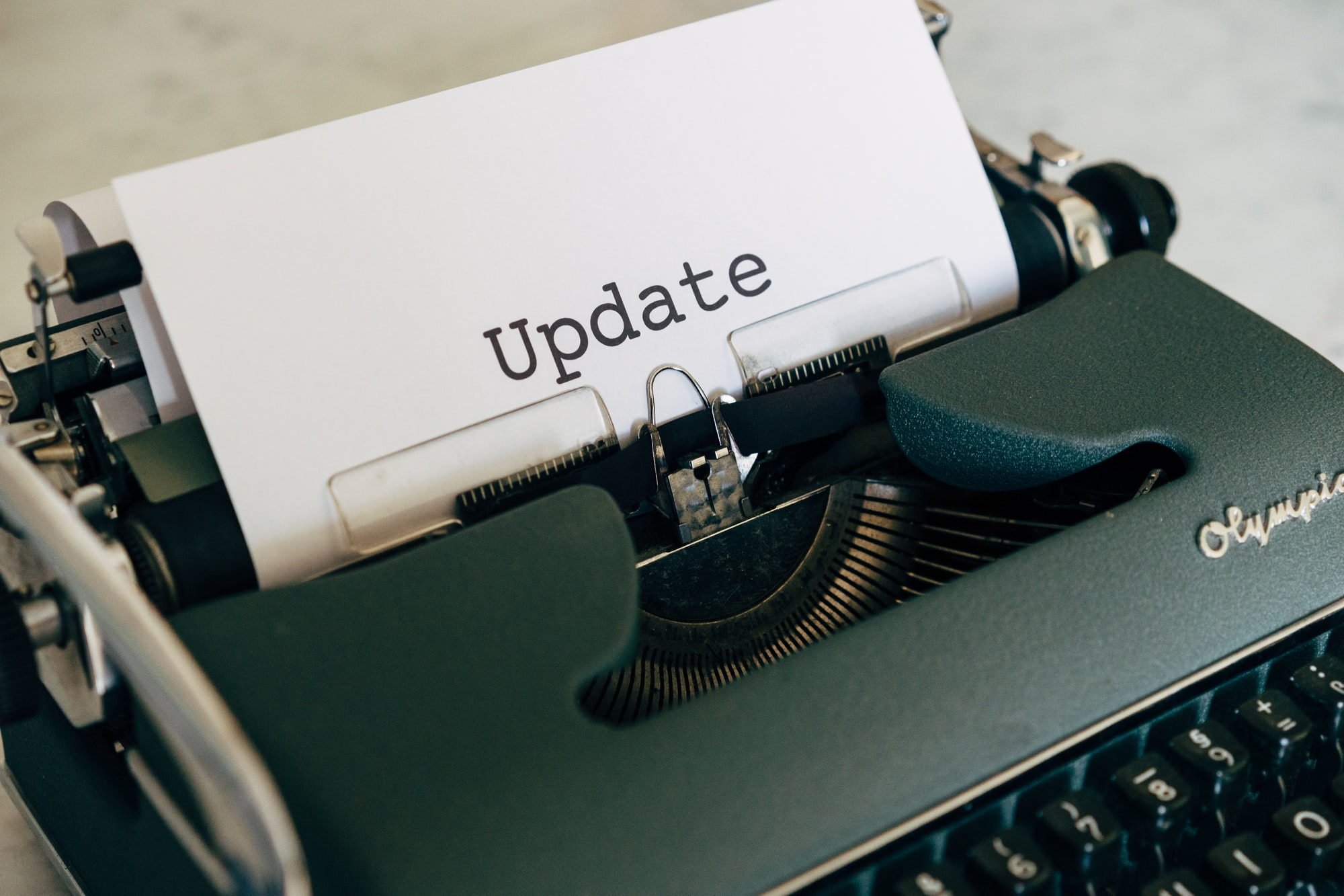 A typewriter with a sheet of paper that says the word 'Update'