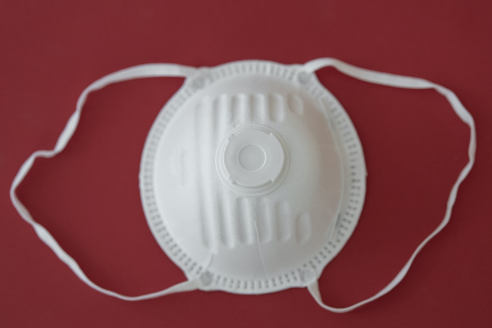 white round plastic lid on red textile
