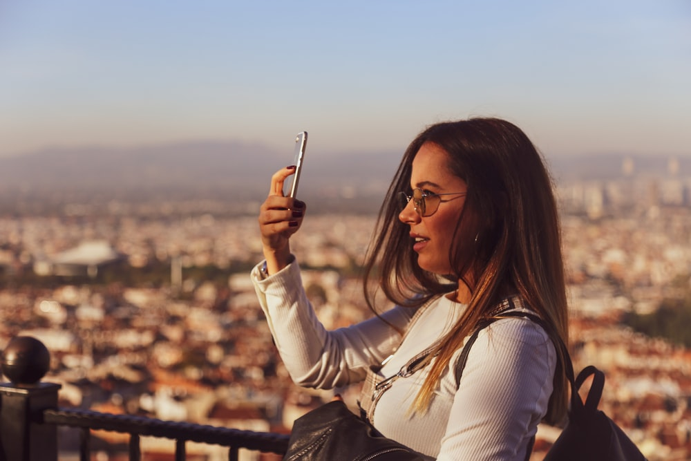 woman in white long sleeve shirt holding smartphone