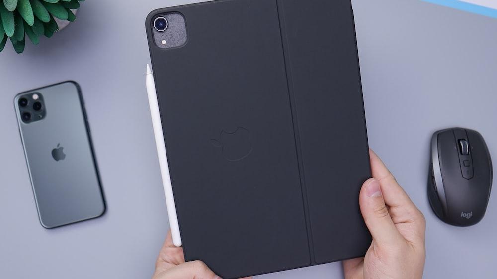 person holding black ipad smart case