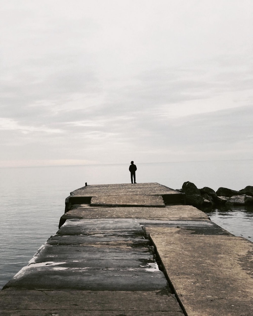 person standing on concrete dock near body of water during daytime
