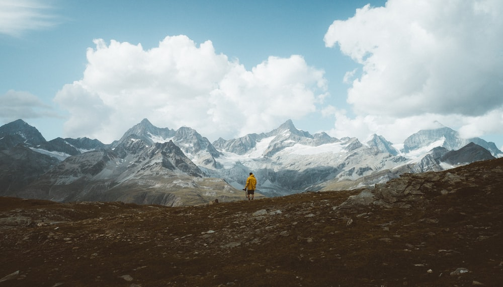 person in yellow jacket walking on brown field near snow covered mountain during daytime