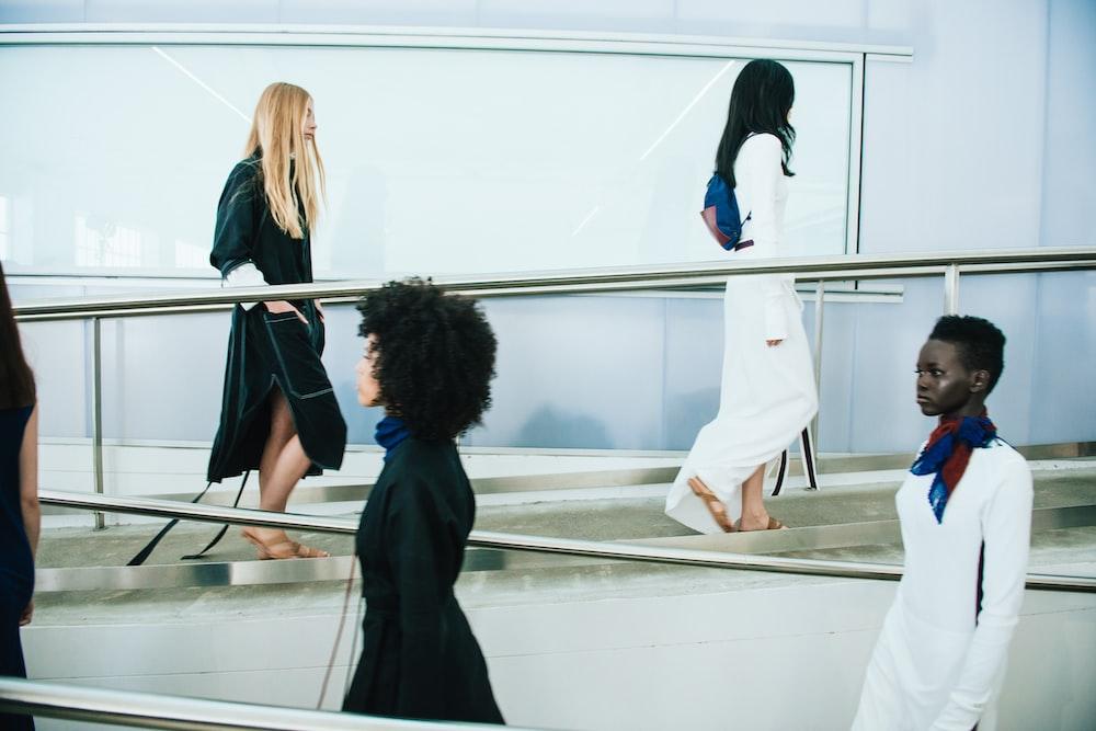 2 women in black coat standing in front of glass wall