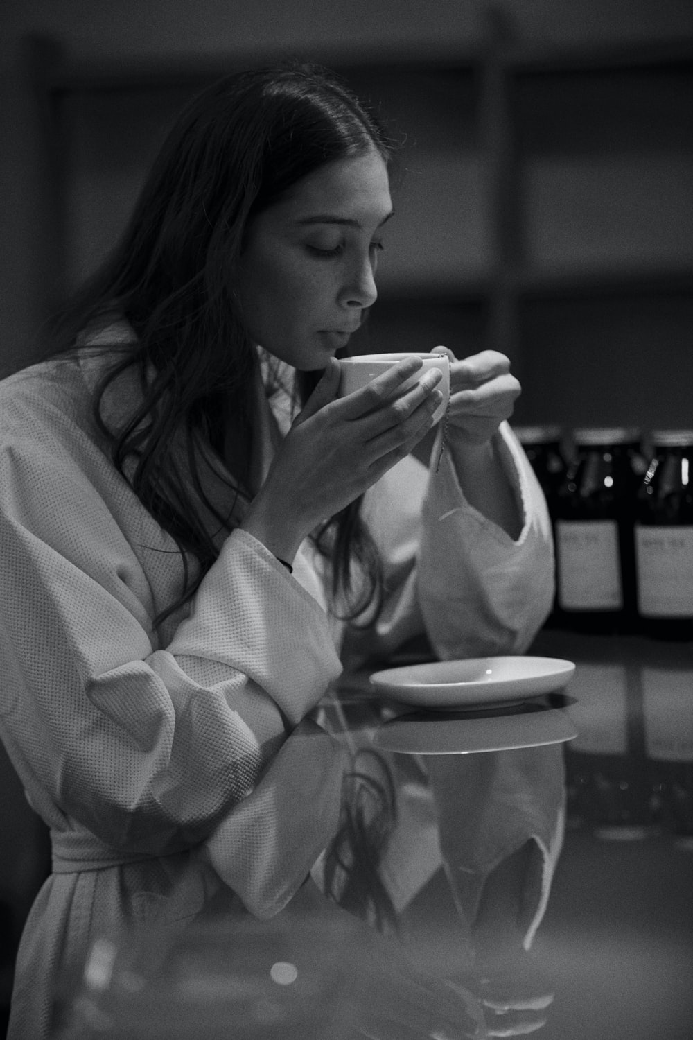 grayscale photo of woman in white robe eating