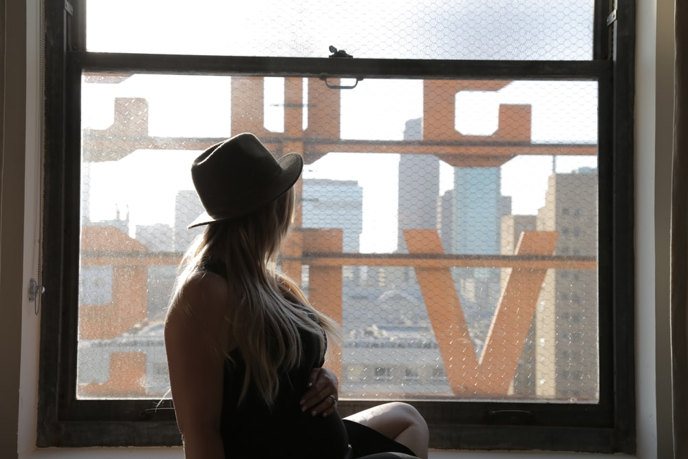 黒のタンクトップと茶色の木製のベンチに座っている黒のフェドーラ帽の女性
