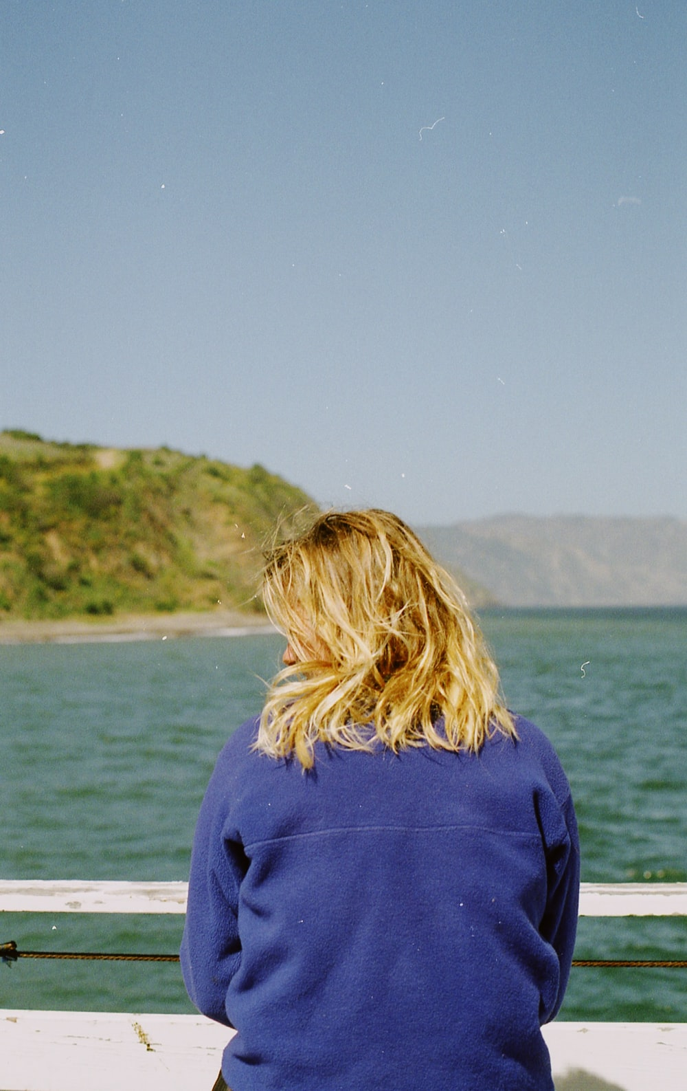 woman in purple hoodie standing near body of water during daytime