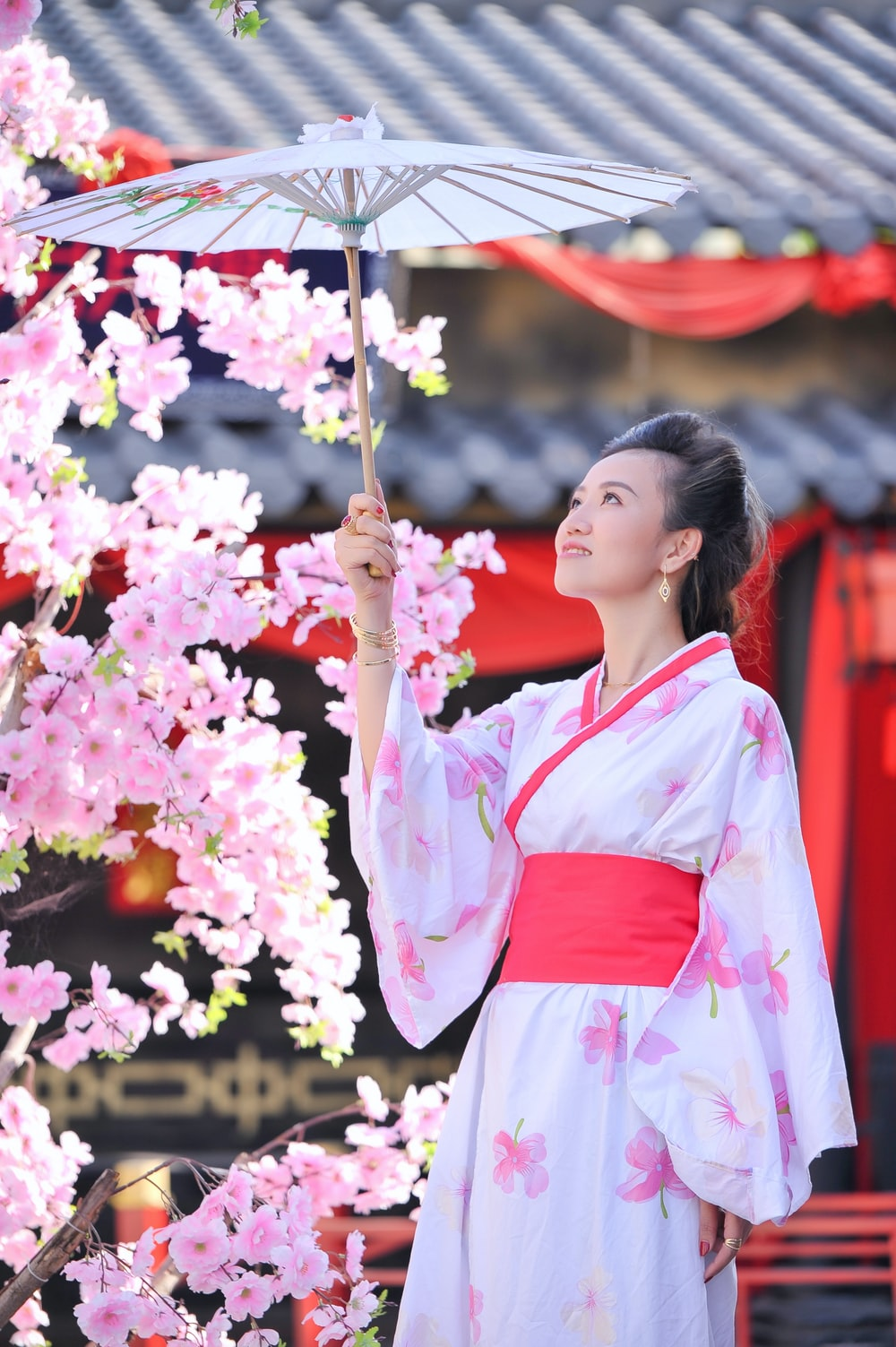 woman in white and red kimono holding pink flowers