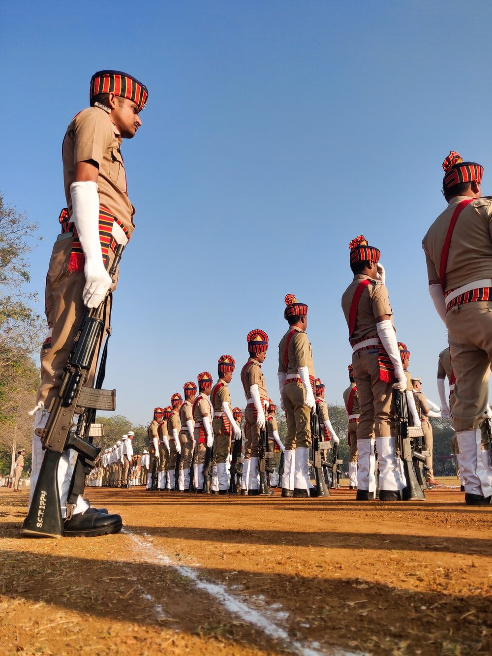 people in brown and white uniform holding airsoft rifle during daytime