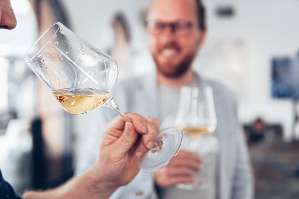 man in white sweater holding clear wine glass