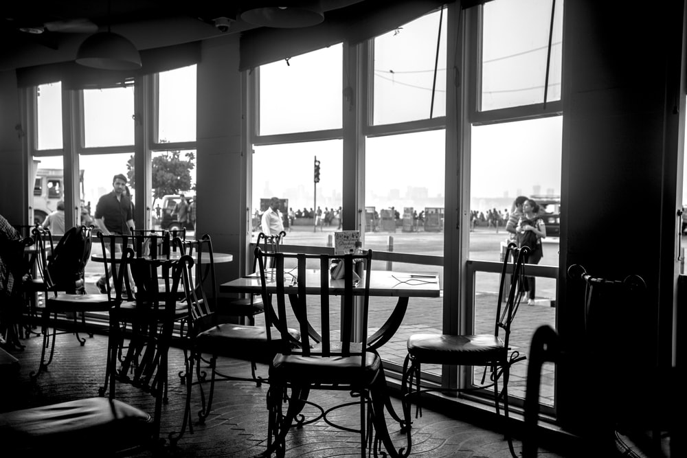 silhouette of people sitting on chairs near window