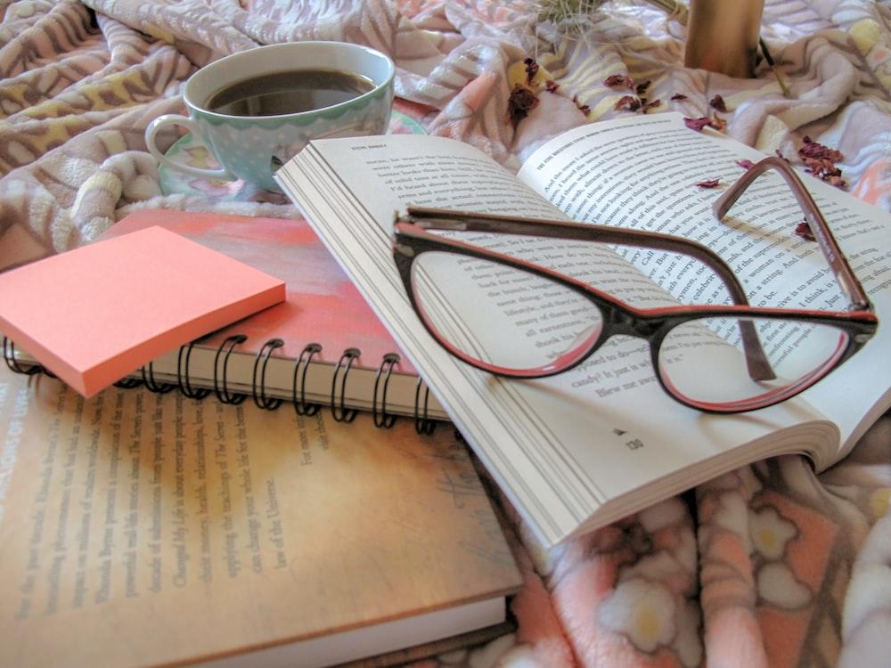 brown framed eyeglasses on white notebook