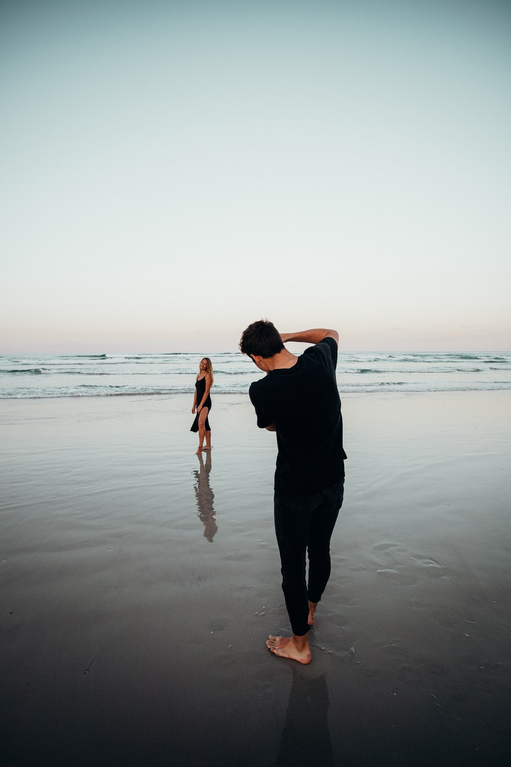 man in black shirt and pants standing on seashore during sunset