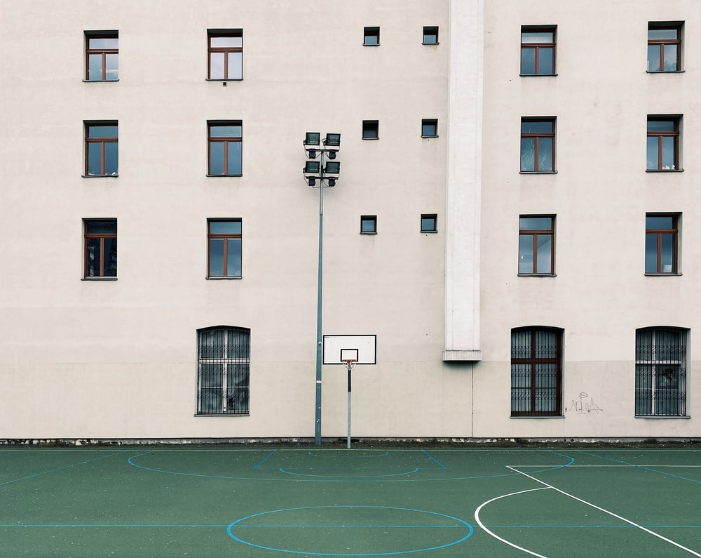 basketball court in front of white concrete building