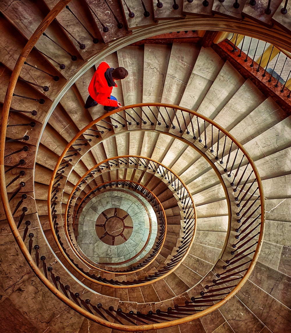 person in red jacket and blue denim jeans standing on spiral staircase