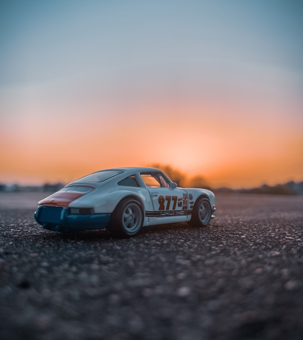 blue and white porsche 911 on gray sand during sunset