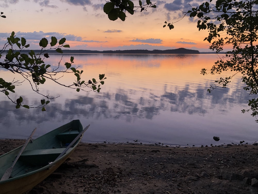 white boat on shore during sunset